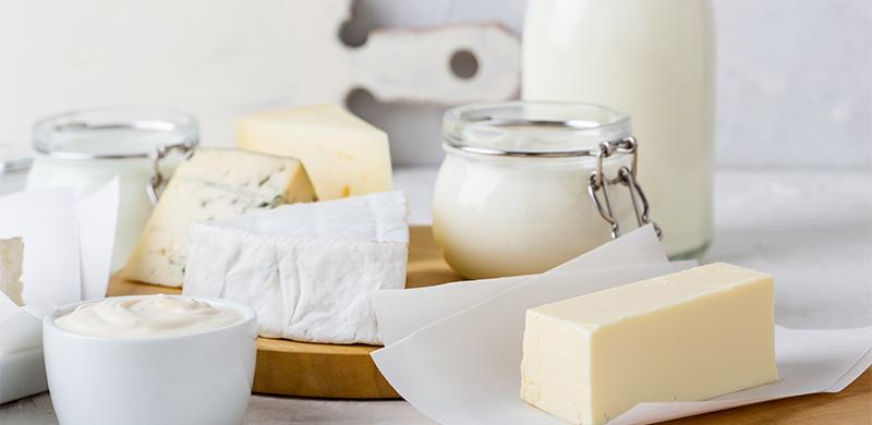 verschiedene Milchprodukte in weißen Verpackungen auf Holzbrettern