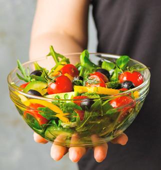 Nahaufnahme Hand hält Glasschale mit Salat