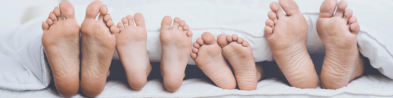 Banner Füße einer Familie, die im Bett liegt