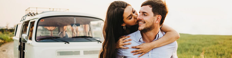 Frau küsst Mann vor Bulli