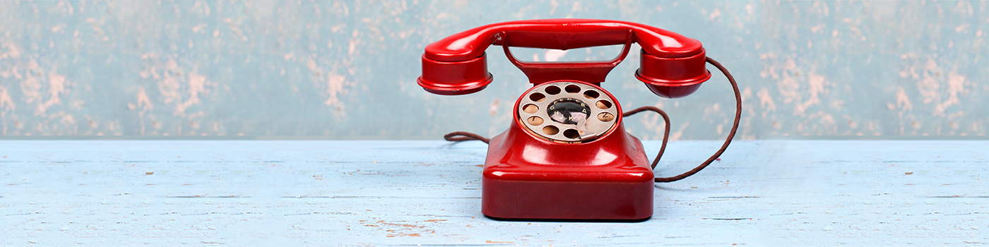 rotes Telefon auf hellem Holz vor leicht gemusteter Wand