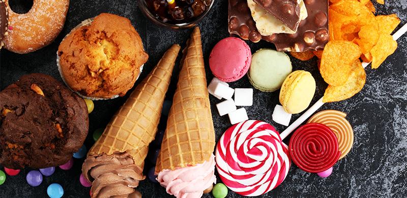 Verschiedene süße und salzige Speisen wie Eis, Lolli, Muffins, Chips