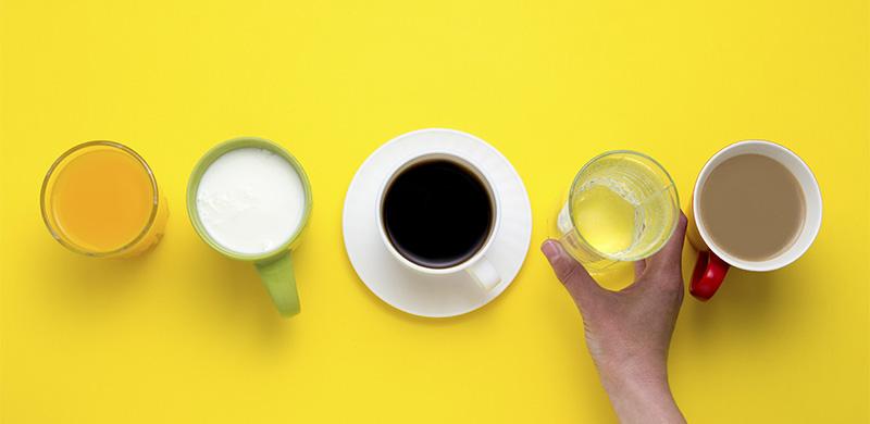 fünf verschiedene Getränke in einer Reihe vor gelbem Hintergrund, Hand greift ein Getränk