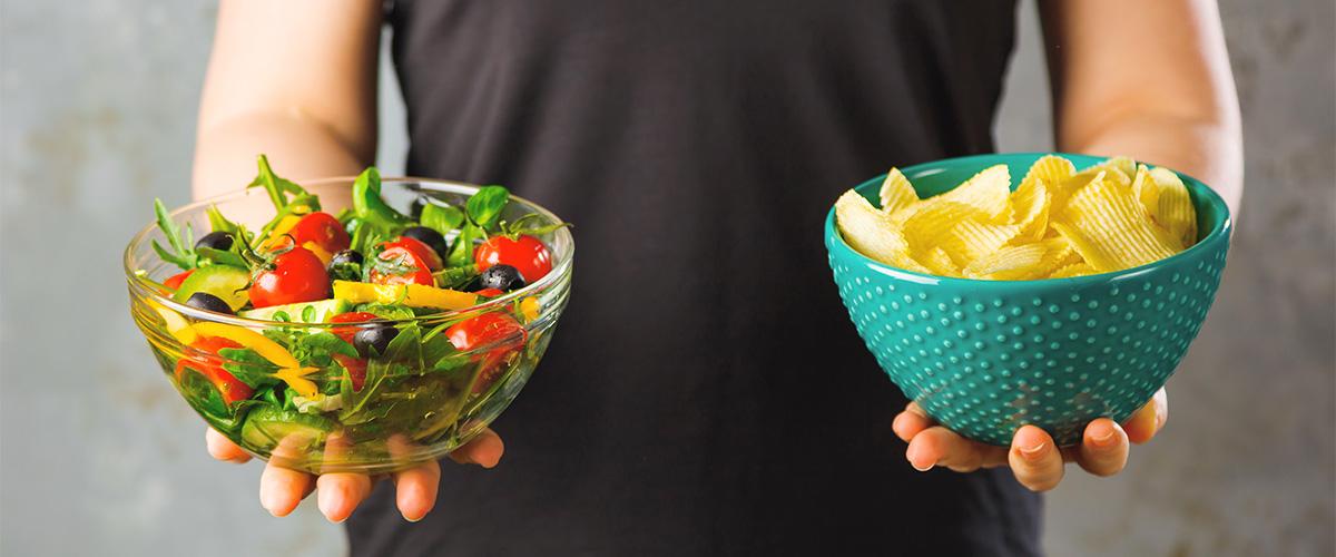 zwei Schüsseln werden gehalten Glasschüssel mit Salat und Keramitschüssel mit Chips