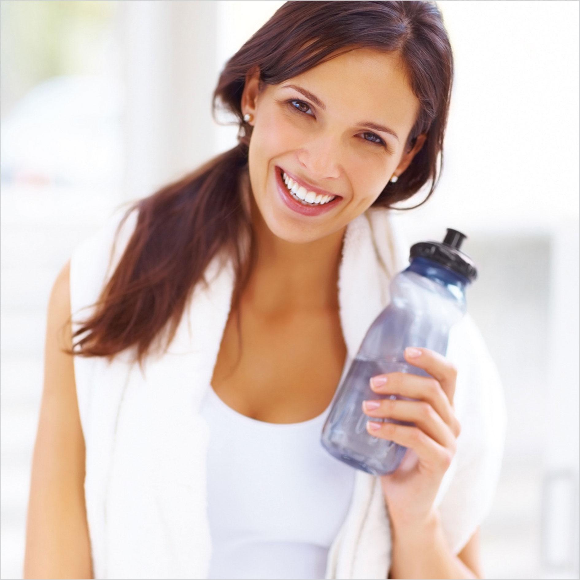 Frau in Sportoutfit mit Wasserflasche in Hand lächelt